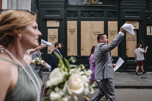 A wedding party marches by boarded-up buildings in the French Quarter in New Orleans on Saturday.
