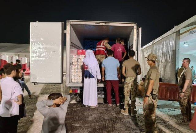 這是一張由一名被撤離的阿富汗人拍攝的照片,該人出於擔心被報復而要求匿名。照片上,烏代德空軍基地人員正在為到達的阿富汗人卸下供給。