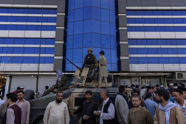 Taliban fighters guarding Kabul's main currency exchange last week.