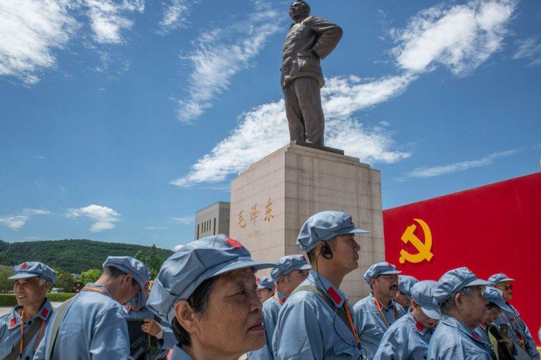陕西省一座毛泽东塑像下身穿红军军装的旅游者。