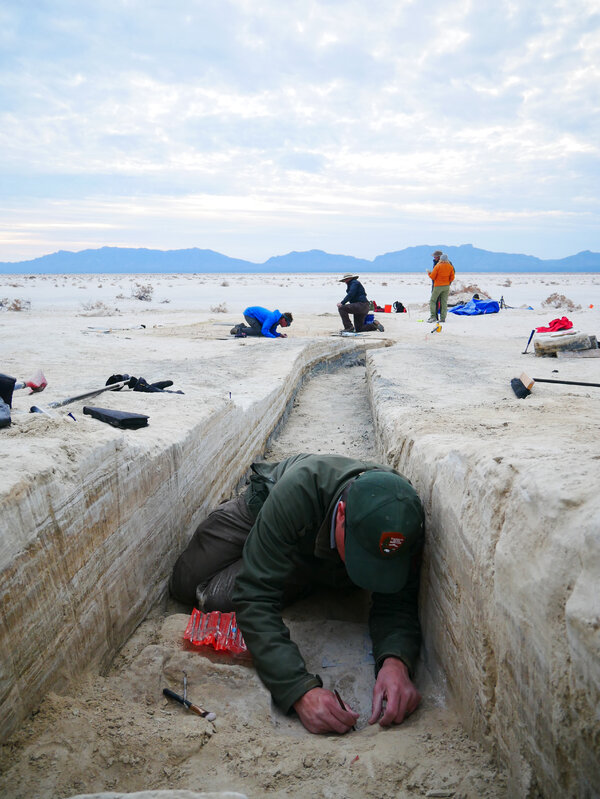 Researchers work on excavating a footprint in the bottom of a trench.