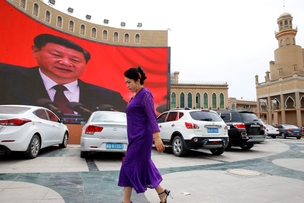 An ethnic Uighur woman walks in front of a giant screen with a picture of Chinese President Xi Jinping in the main city square in Kashgar in Xinjiang Uighur Autonomous Region, China. The screen broadcasts a slideshow of images of Xi on loop, including propaganda images of his previous visit to Xinjiang.