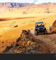 merzouga morocco feb 21 2016 blue polaris rzr 800 crossing a mountain road in [ 1500 x 1120 Pixel ]