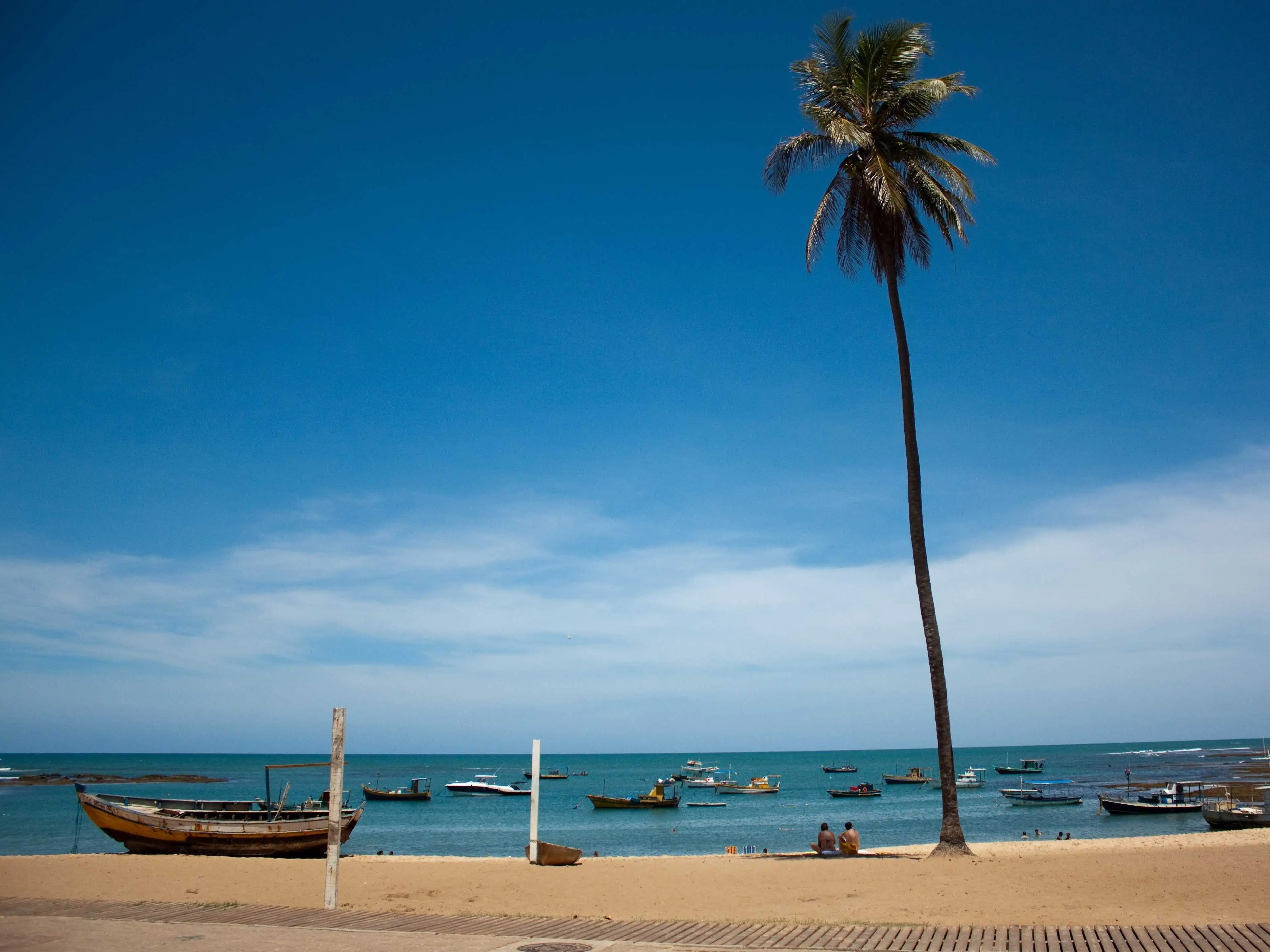 An old fishing village-turned-resort-style beach, the beautiful Praia do Forte in Bahia, Brazil, features colorful boats and small, lazy waves.