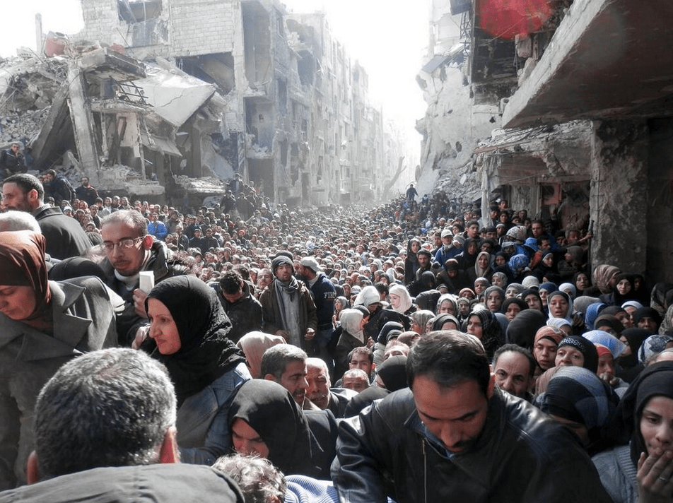 Residents wait to receive food aid distributed at the besieged al-Yarmouk camp, south of Damascus on January 31, 2014. (UNRWA)