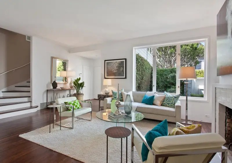 Inside, a living room looks out onto a green backyard.