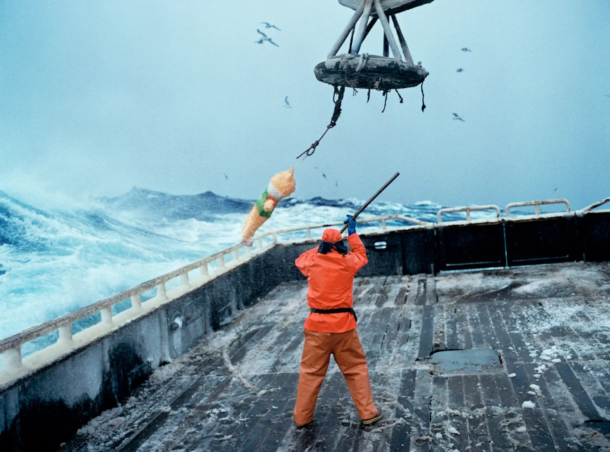 """There are a lot of near misses even on the safest of crab boats,"" Arnold says. One time, a crane was lifting a crab pot onto the Rollo's deck when it went over the crab sorting table, where Arnold and other crew members were sorting. As the pot went over, the cable on the crane snapped. The 800-pound pot fell on top of the table, just missing Arnold and his crew members. Here, we see the crane in happier times, as a crew member hits a pinata."