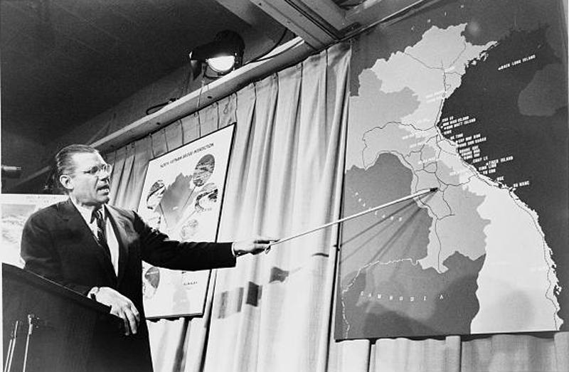 Secretary of Defense Robert McNamara pointing to a map of Vietnam at a press conference