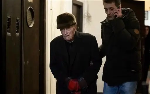 Former communist prison commander Alexandru Visinescu leaves his home escorted by a police officer dressed in civilian clothes, in Bucharest, Romania, Wednesday, Feb. 10, 2016. A Romanian appeals court has upheld a 20-year prison sentence for Visinescu, a 90-year-old communist-era prison guard convicted of crimes against humanity, the most high-profile case since dictator Nicolae Ceausescu was tried and executed in 1989. (AP Photo/Andreea Alexandru) ROMANIA OUT