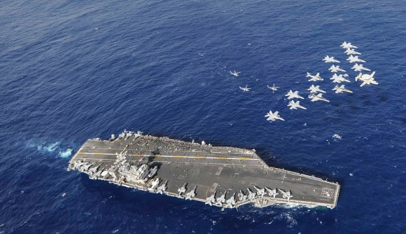 Aircraft assigned to Carrier Air Wing 11 perform a fly-by performance for Sailors and their family members on a tiger cruise aboard the aircraft carrier USS Nimitz.
