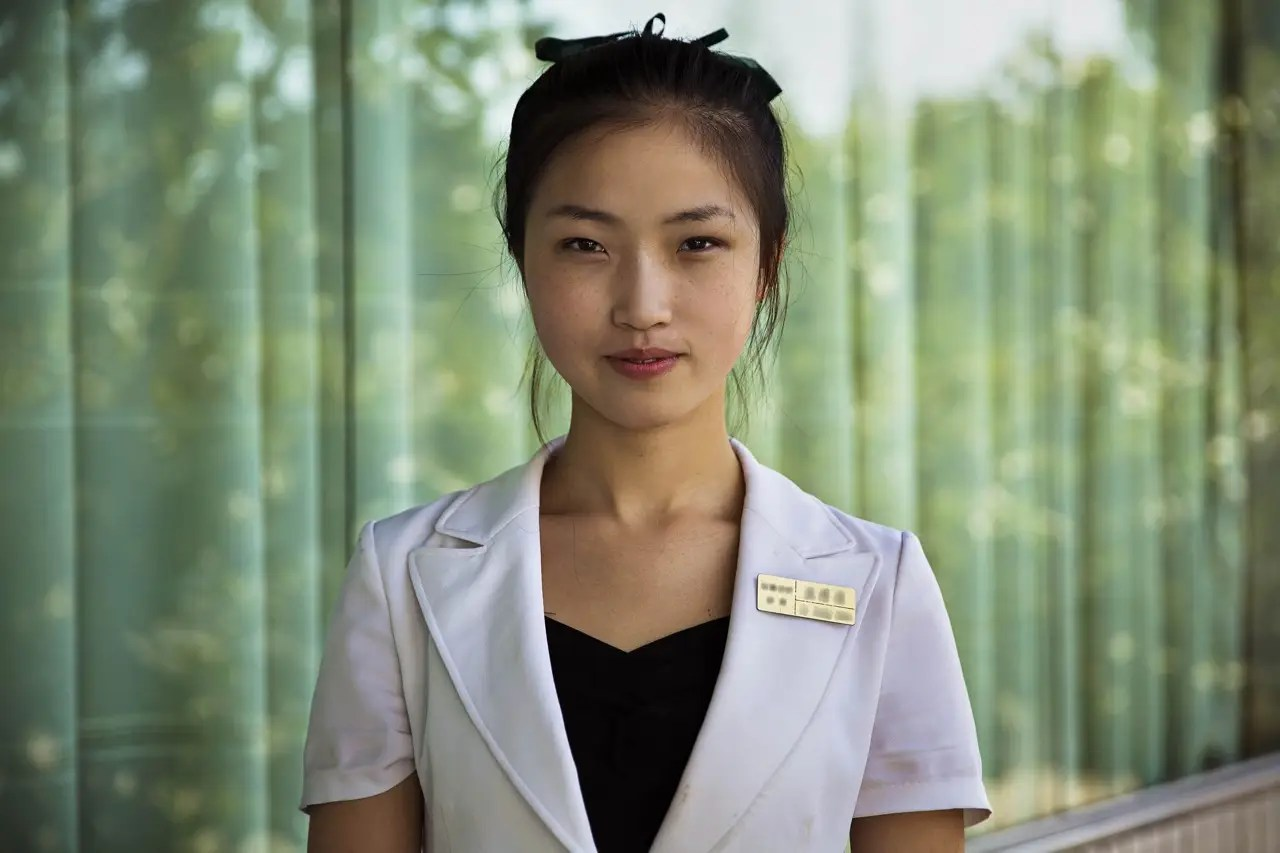 """Going to North Korea was like """"stepping [onto] a totally different planet, with different rules,"""" Noroc says. This woman was photographed in Pyongyang, North Korea."""