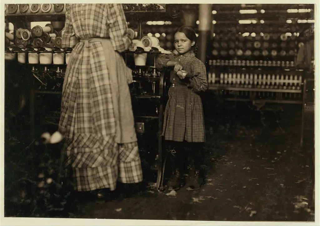 "Little Fannie, 7 years old, 48 inches high, helps sister in Elk Mills. Her sister (in photo) said, ""Yes, she he'ps me right smart. Not all day but all she can. Yes, she started with me at six this mornin'."" These two belong to a family of 19 children. Taken in Fayetteville, Tennessee, November 1910."