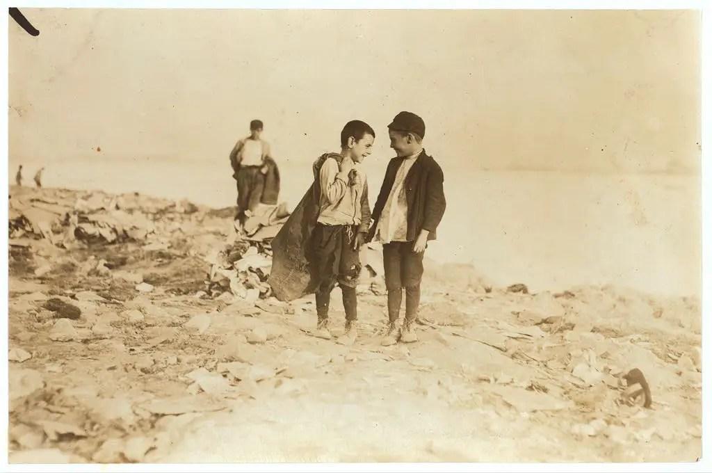 "Boys picking over garbage on ""the Dumps."" Location: Boston, Massachusetts, October 1909."