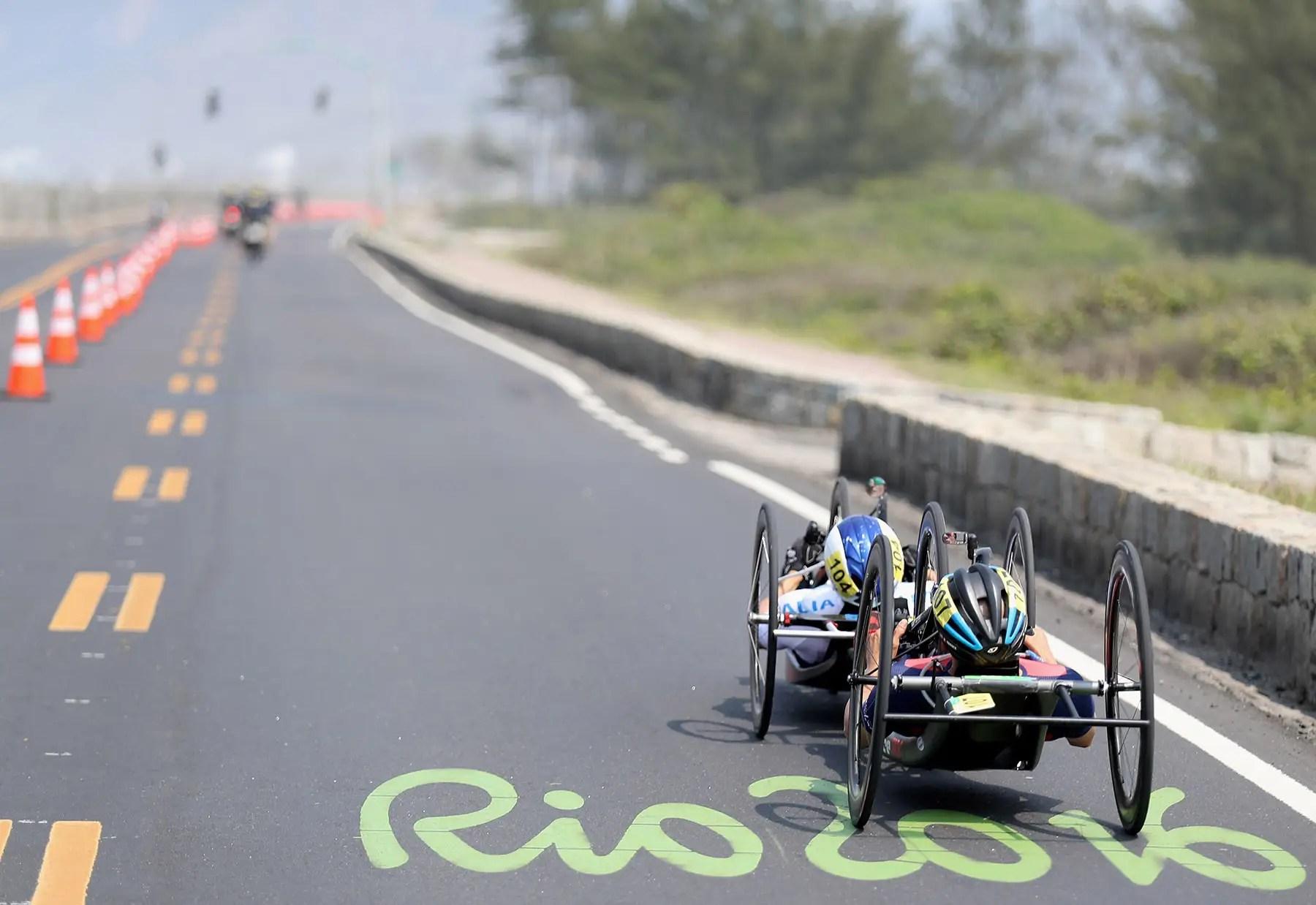 Dos corredores en silla de ruedas compiten en una carrera de ruta.