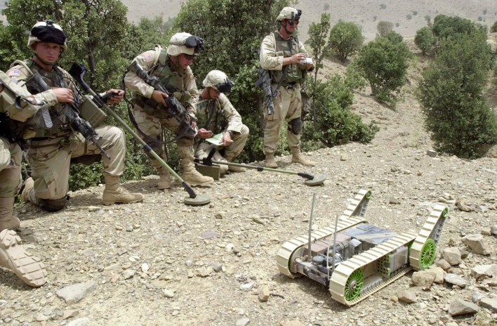 Land-mine detectors stand by as a US Army soldier, right, maneuvers Hermes the robot into a cave to detect mines, traps, and other unexploded ordnance as well as weapons or equipment possibly hidden by Taliban or al-Qaida fugitives in the eastern border town of Qiqay, Afghanistan, Monday, July 29, 2002.