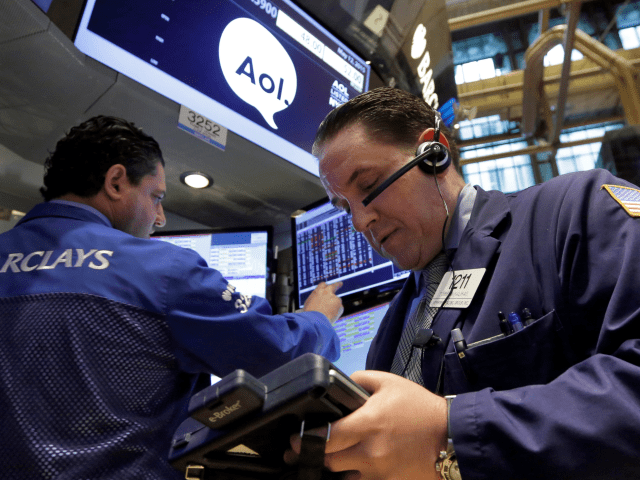 Specialist Ronnie Howard, left, and trader Tommy Kalikas work at the post that handles AOL on the floor of the New York Stock Exchange, Tuesday, May 12, 2015. Verizon is buying AOL for about $4.4 billion, advancing the telecom's push in both mobile and advertising fields.