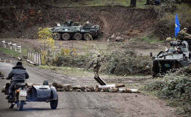 A man on a motorcycle with a sidecar approaches a Russian surveillance point in the town of Shusha, intended to control the ceasefire.