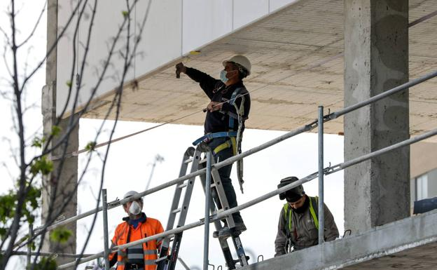 Several workers work on the construction of a building, in a file image.
