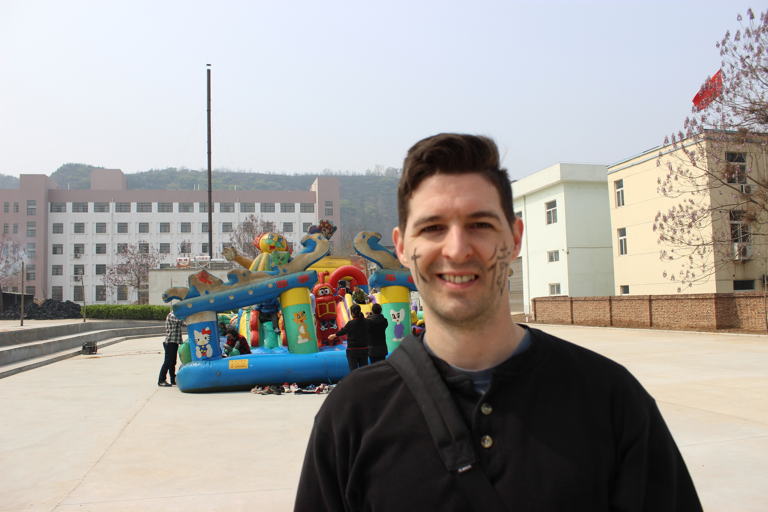 Dave with his Mandarin name on his cheeks in front of the bouncy castle.
