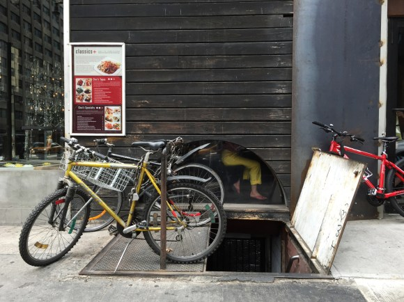 A woman dines at an asian restaurant in yellow pants, matching the yellow deliverybike just outside.