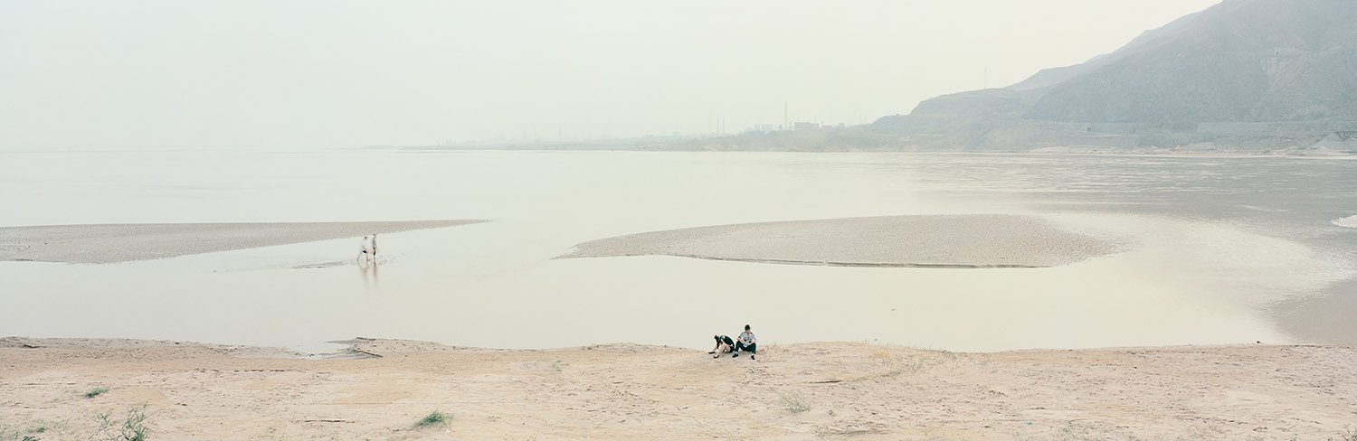 Banks of the Yellow River. Hejin, Shanxi, China, 2011.  A couple sits by the banks of the only remaining undeveloped section of the Yellow River on the outskirts of the small city of Hejin. Although China has roughly the same amount of water as the United States, its population is nearly five times greater, making water a precious and increasingly sought-after resource. The heavily industrialized area around Hejin contains some of the most polluted waters in the river. In 2007, after surveying the river, the Yellow River Conservancy Commission stated that one third of the river system had pollution levels that made the water unfit for drinking, aquaculture, industrial use, or even agriculture.