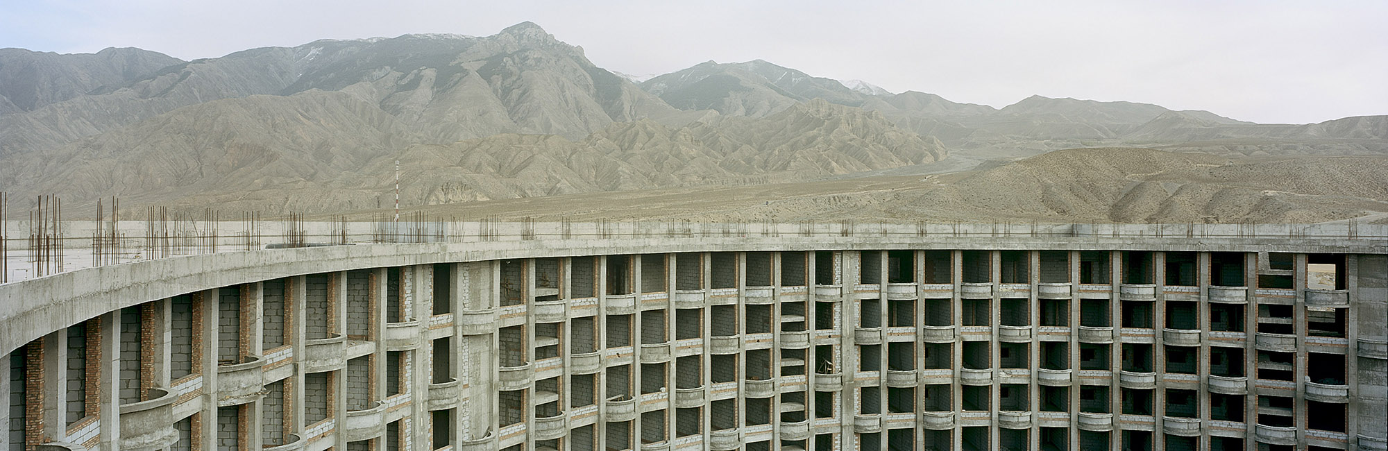 """Abandoned 5 Star Hotel Construction. Guide,Qinghai, China. 2014   One of the benefits of creating the Sanjiangyuan National Nature Reserve, according to China's State Council, would be """"ecological protection and construction"""" on the plateau. Development in the protected ecosystem of the Reserve, however, soon extended beyond tourism, to the mining of gold and other minerals, road construction, and real estate development. Meanwhile some of the tourism-related projects were lost to changing political winds: according to a local security guard, construction on this 5-star hotel came to a halt when developers couldn't secure the necessary permits after a turnover in local government personnel. While much new construction in the area has reached completion, scientists have raised concerns that large towns and cities, and the infrastructure that connects them create higher densities of humans that will inevitably increase the stress on the local ecology."""