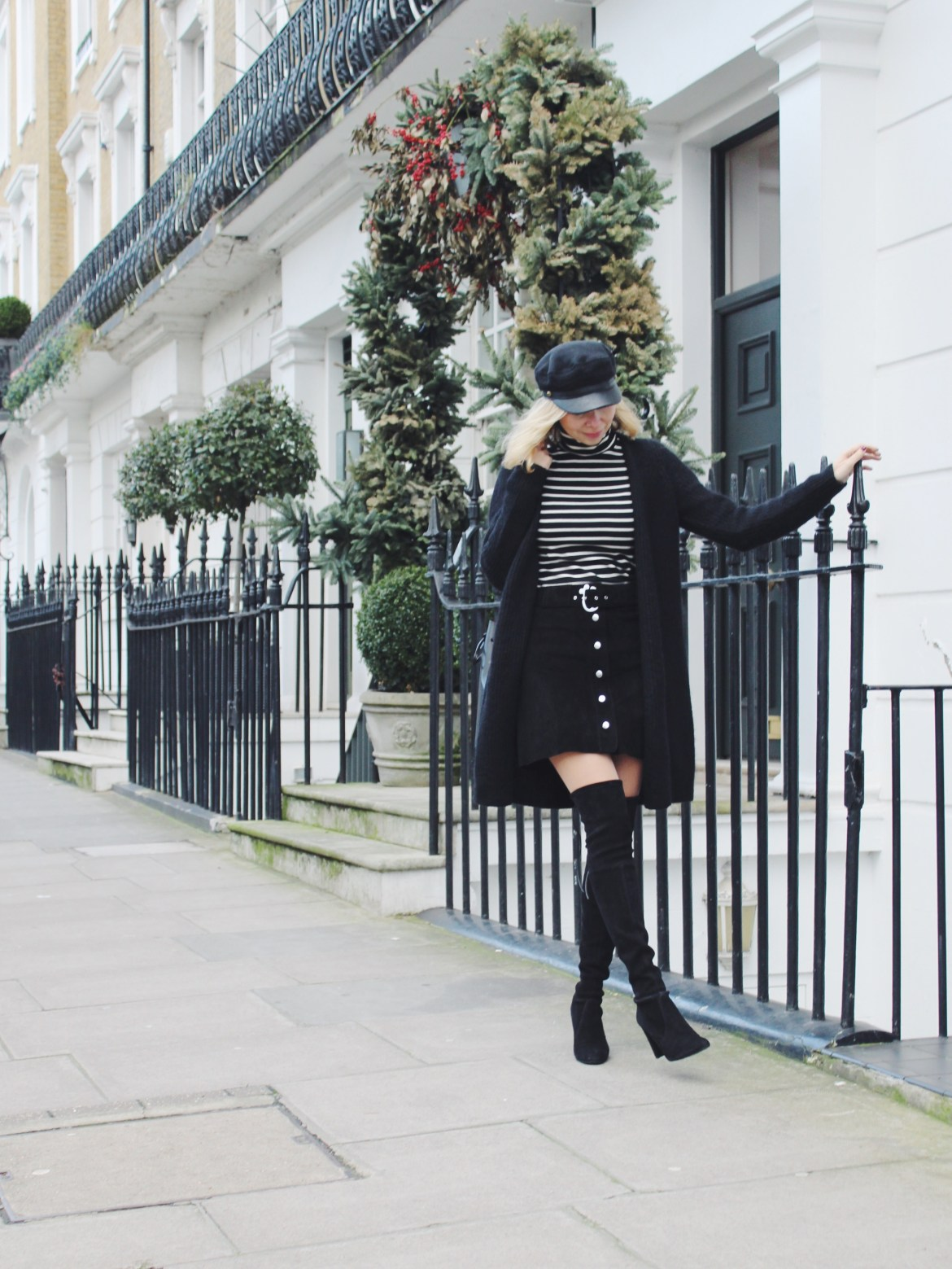 Arianna Trapani is wearing stripe top from Le Petit Bateau, black suede skirt from Zara, black knitted cardigan from Cos, Highland boots from Stuart Weitzman, Black bucket bag from Mansur Gavriel, Bake boy hat from Eugene Kim.