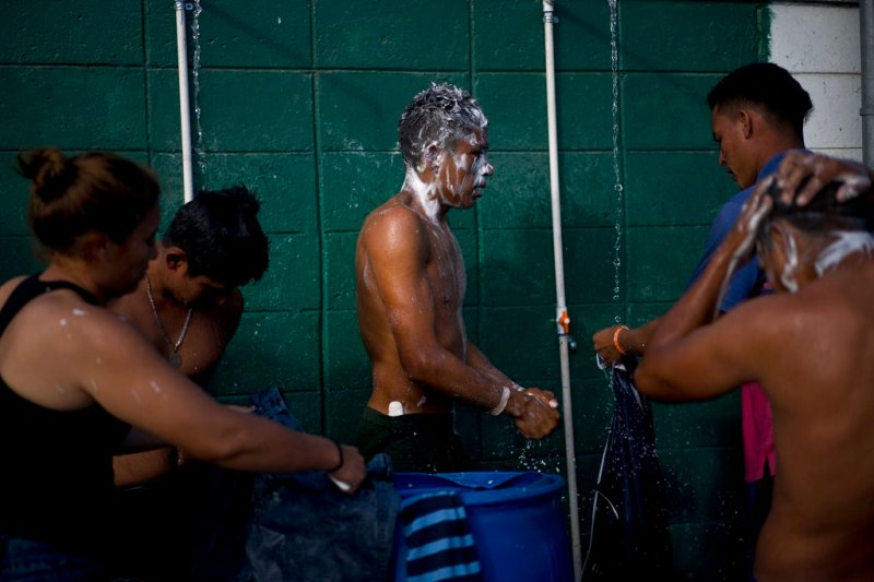 Migrants, part of the migrant caravan, take a bath at a sports complex where more than 5,000 Central American migrants are sheltering in Tijuana, Mexico, Wednesday, Nov. 28, 2018. As Mexico wrestles with what to do with the thousands of people camped out in the border city of Tijuana, President-elect Andres Manuel Lopez Obrador's government signaled that it would be willing to house the migrants on Mexican soil while they apply for asylum in the United States, a key demand of U.S. President Donald Trump. (AP Photo/Ramon Espinosa)