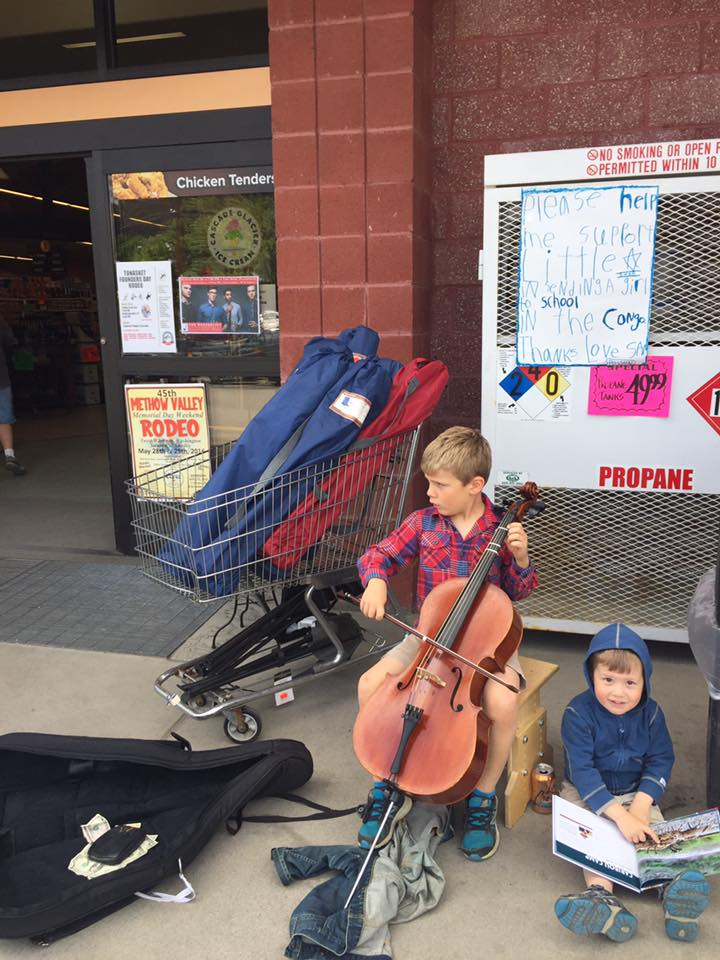 Sam plays cello outside the grocery store to raise money to send a young girl to school in the Democratic Republic of the Congo.