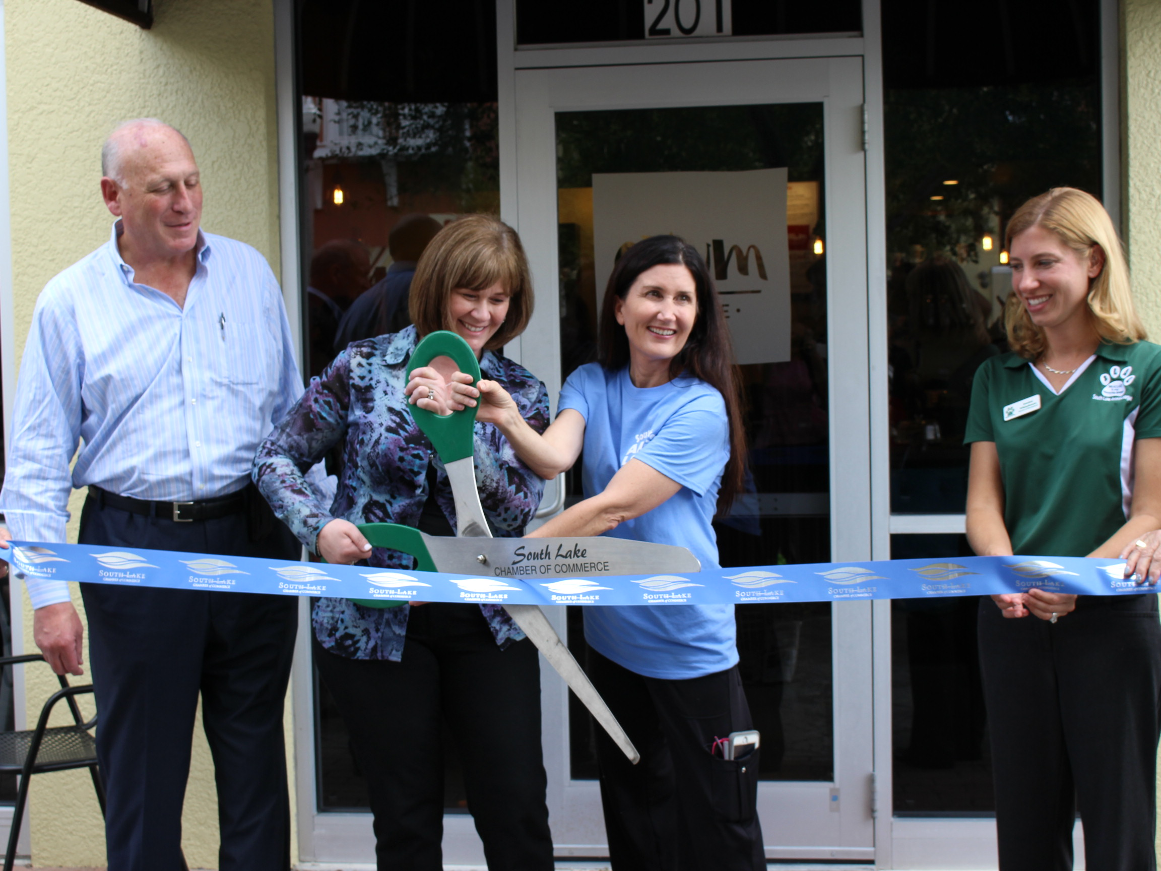 Sandra Cagan, the founder of Orlando Cat Cafe (pictured left), and Jessica Whitehouse, the director of development at The Animal League (pictured right), cut the ceremonial ribbon at the grand opening of Orlando Cat Cafe on Thursday.