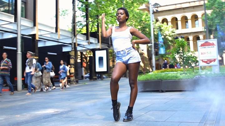 A still of Gloria dancing in Sydney City
