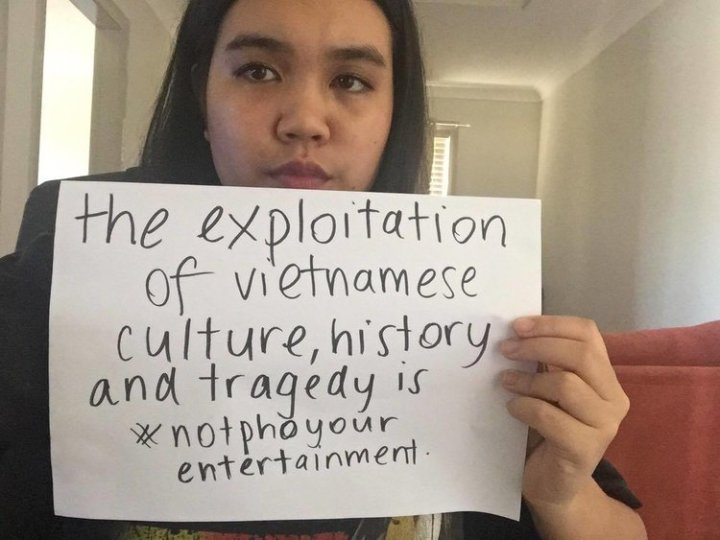 May Tran holding poster that reads: the exploitation of Vietnamese culture, history and tragedy is #notphoyourentertainment