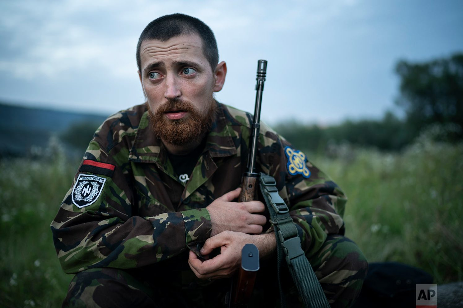 """Yuri """"Chornota"""" Cherkashin, head of Sokil (Falcon), the youth wing of the nationalist Svoboda party, sits with his AK-47 rifle at the """"Temper of will"""" summer camp on July 29, 2018, in a village near Ternopil, Ukraine. """"We never aim guns at people,"""" he tells his campers. """"But we don't count separatists, little green men, occupiers from Moscow as people, so we can and should aim at them."""" (AP Photo/Felipe Dana)"""