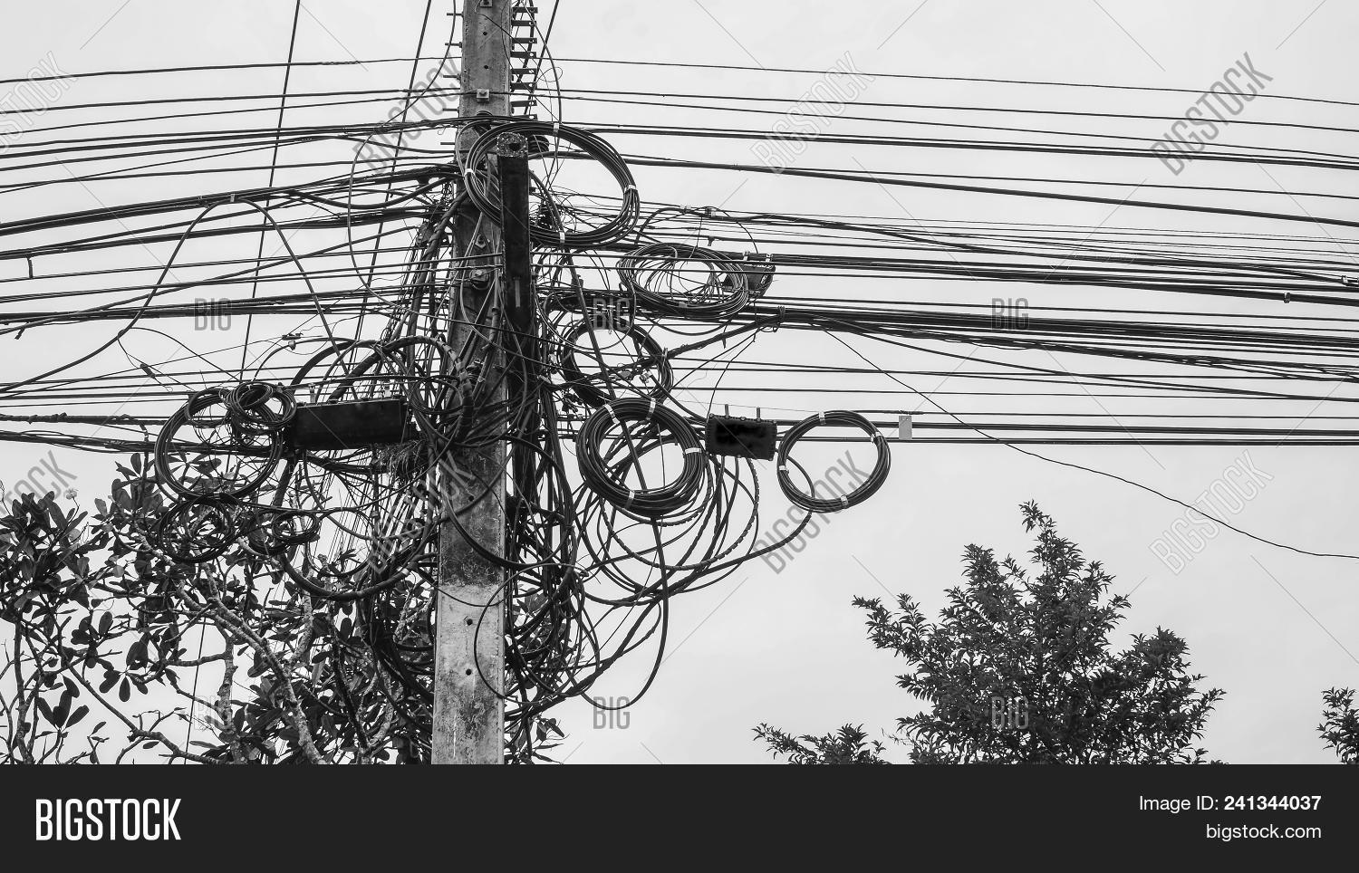 hight resolution of potential danger from a mess of wires at thailand electric pole with electric wire tangled very messy electricity or telephone pole