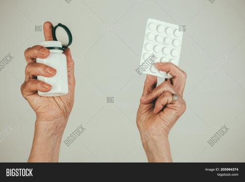small resolution of pills medications hands old female hands hold pills in blister pack and pill bottle packaging