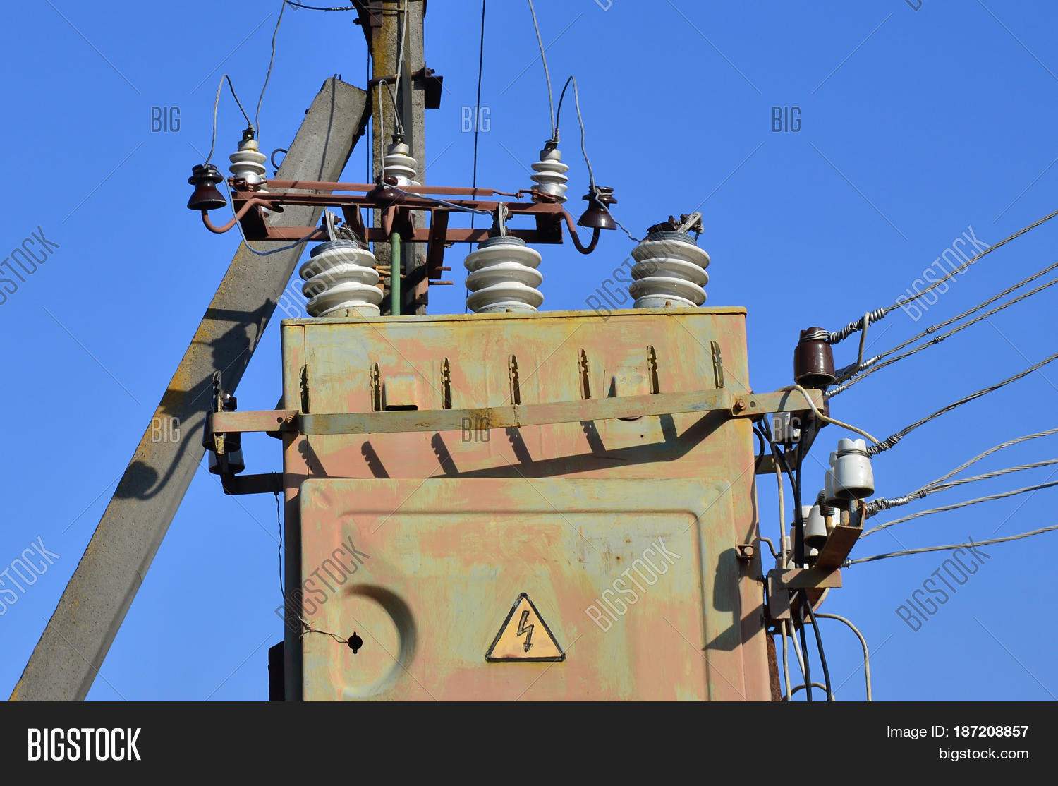 hight resolution of old and obsolete electrical transformer against the background of a cloudless blue sky device for