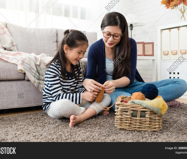 Happy Asian Kids Sitting On The Sofa With Her Mother And Knitting Together In The Living Room At Home