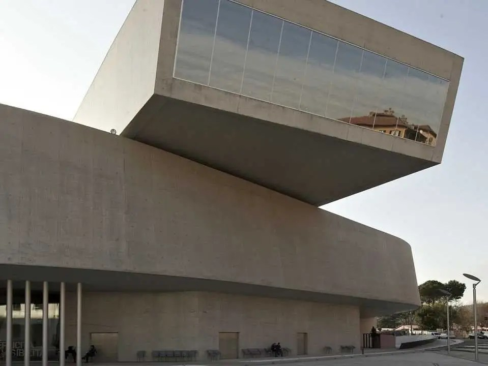 The MAXXI in Rome, Italy took 10 years to build. It has exposed concrete, glass, and steel.