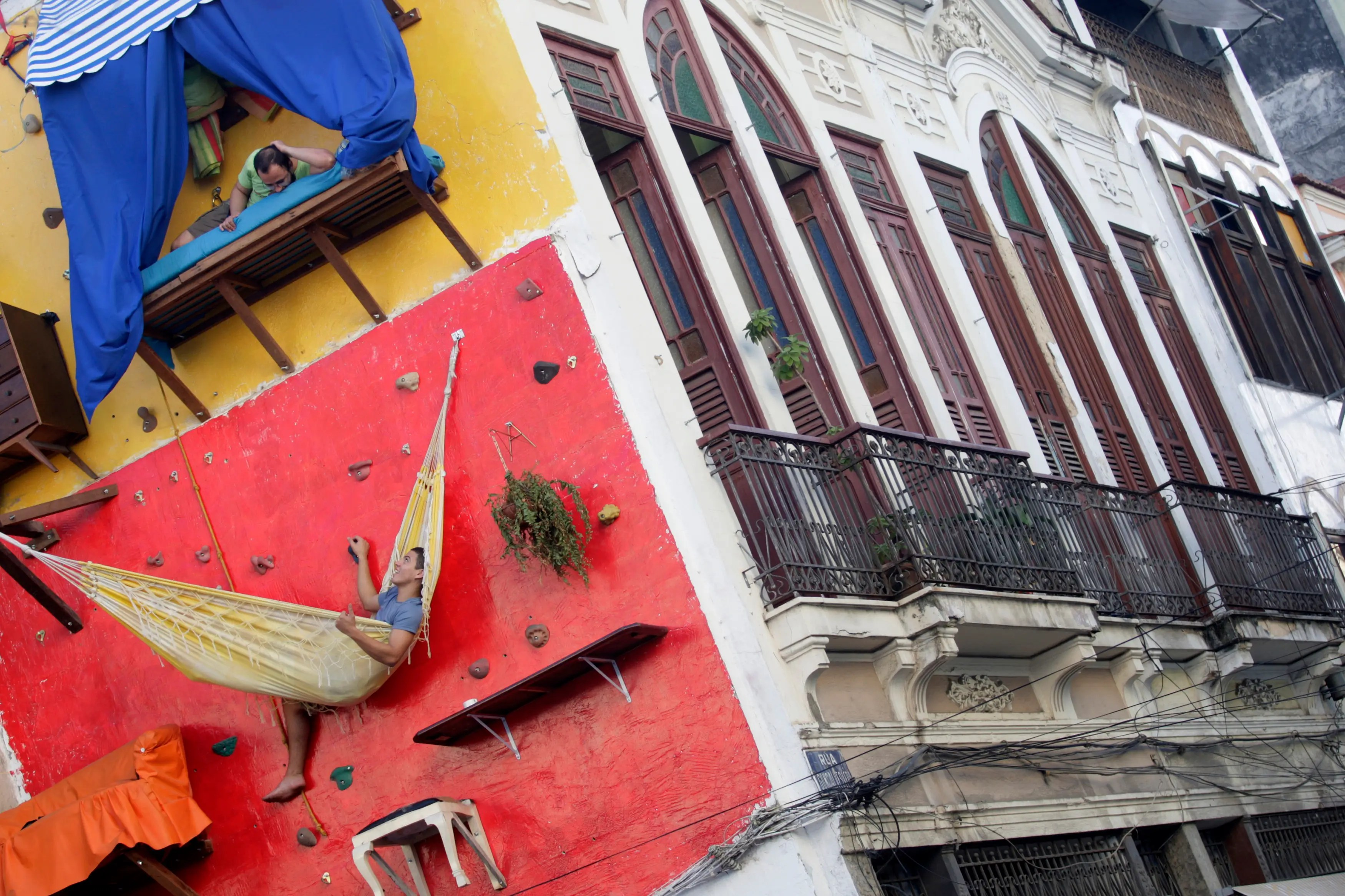 "Brazilian artists Tiago Primo (top) and his brother Gabriel built a vertical ""house"" on a climbing wall in Rio de Janeiro. They had shelves, counters, a hammock and a bed, but used the bathroom inside the art gallery next door."