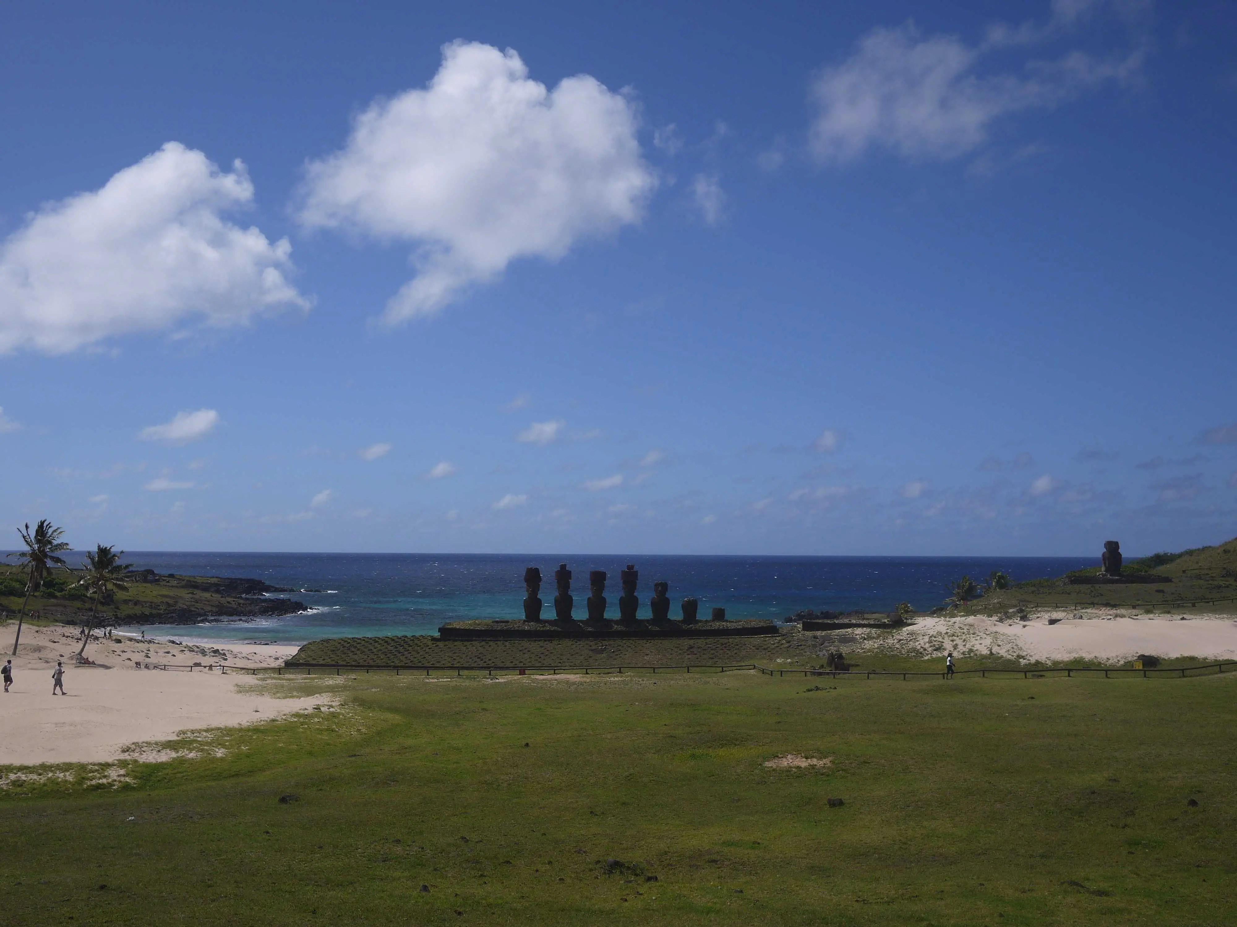 Ancient monolithic Moai statues watch over swimmers at the picturesque Anakena Beach in Easter Island, Chile.