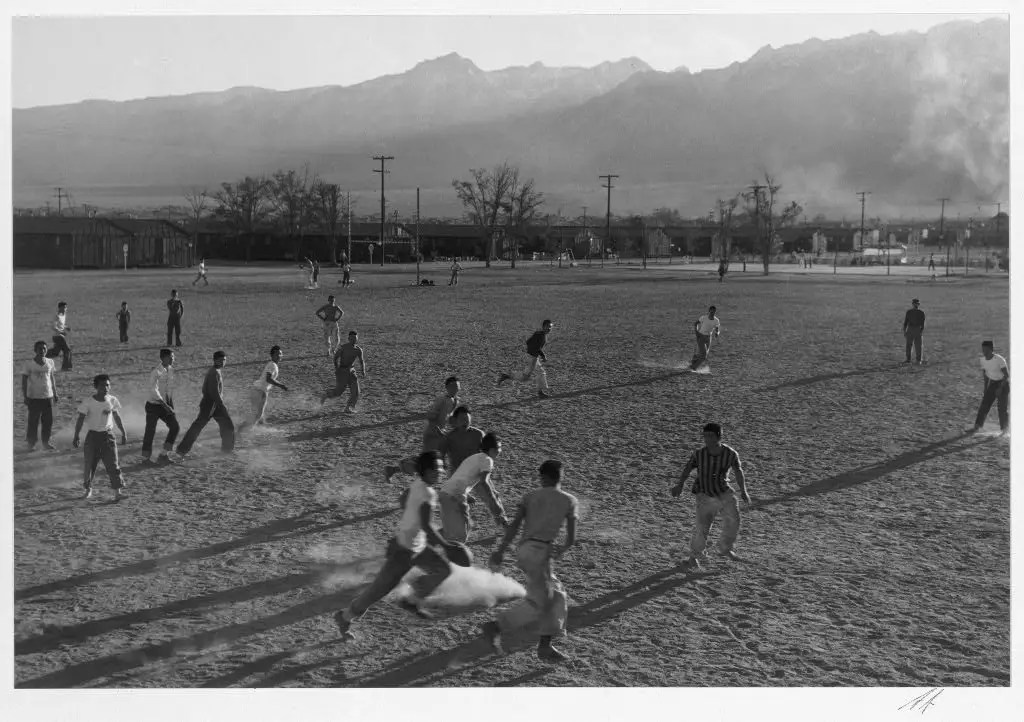 Men play American football on a dusty field.