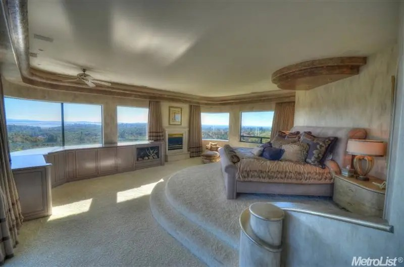 Upstairs, the master bedroom offers sweeping views of the surrounding hills, especially from the elevated bed.