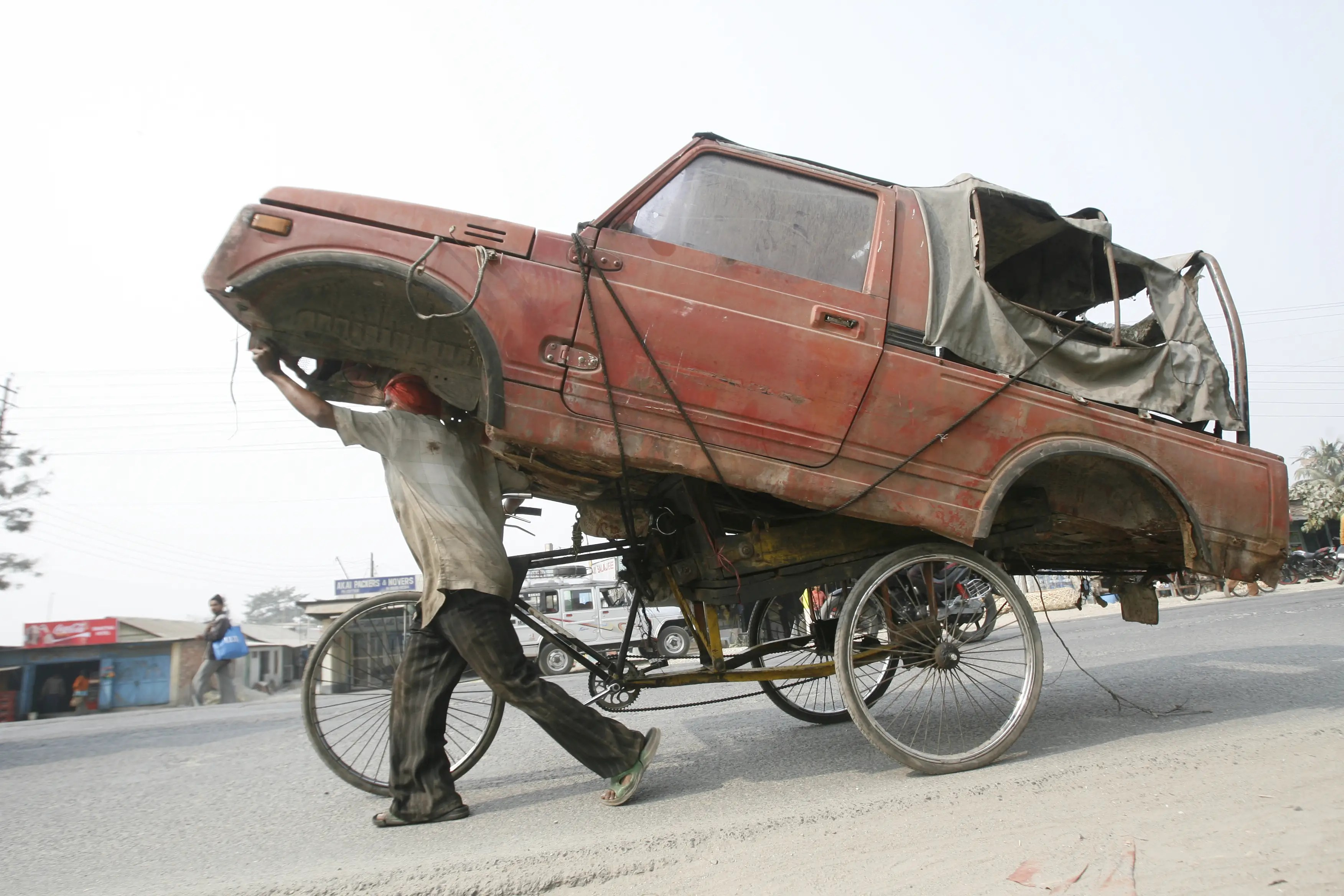 An Indian rickshaw driver is taking a wrecked car for a ride.