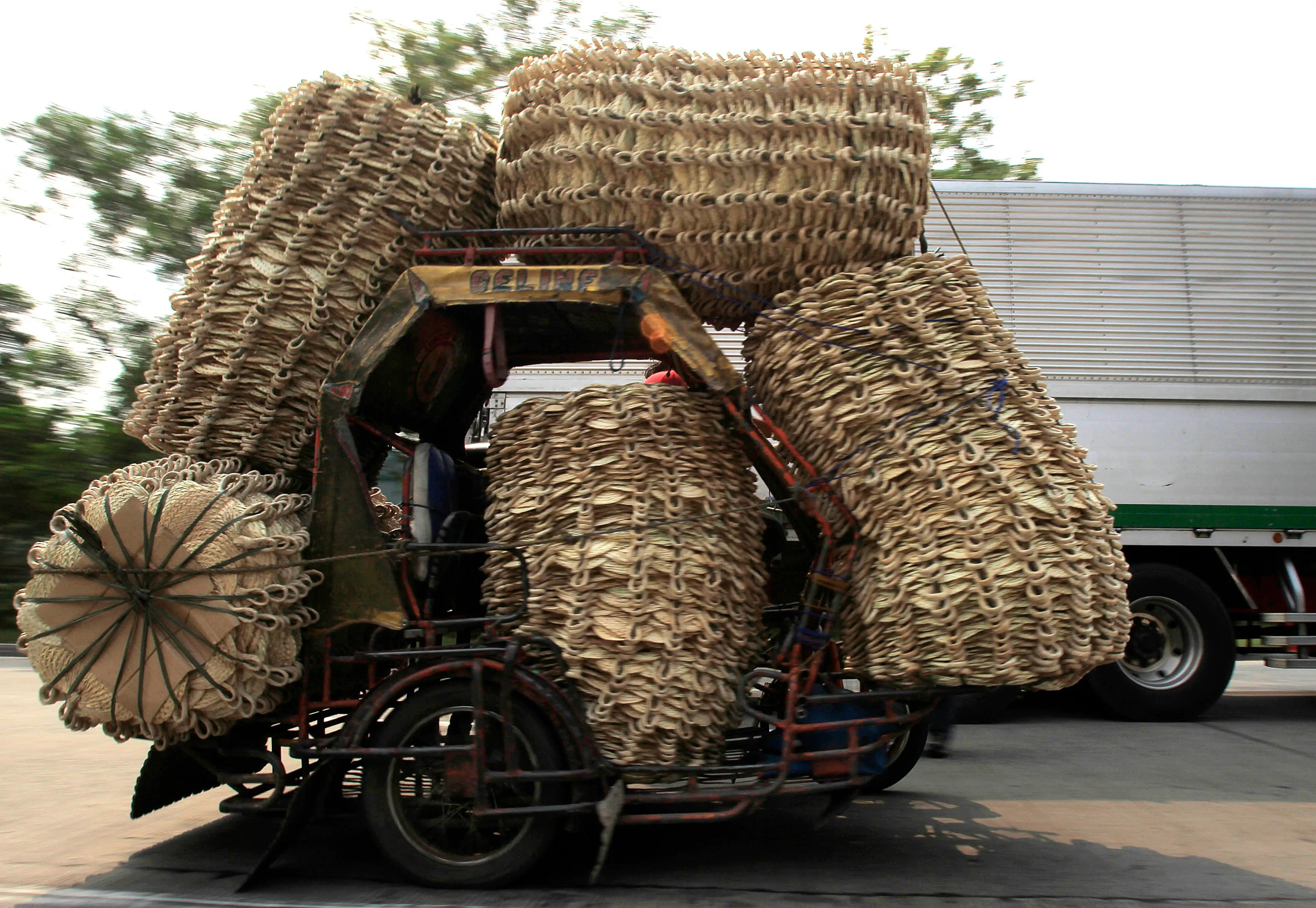 A man pedals his bicycle with a cart full of abaca fans, which he will deliver to a market in Manila.