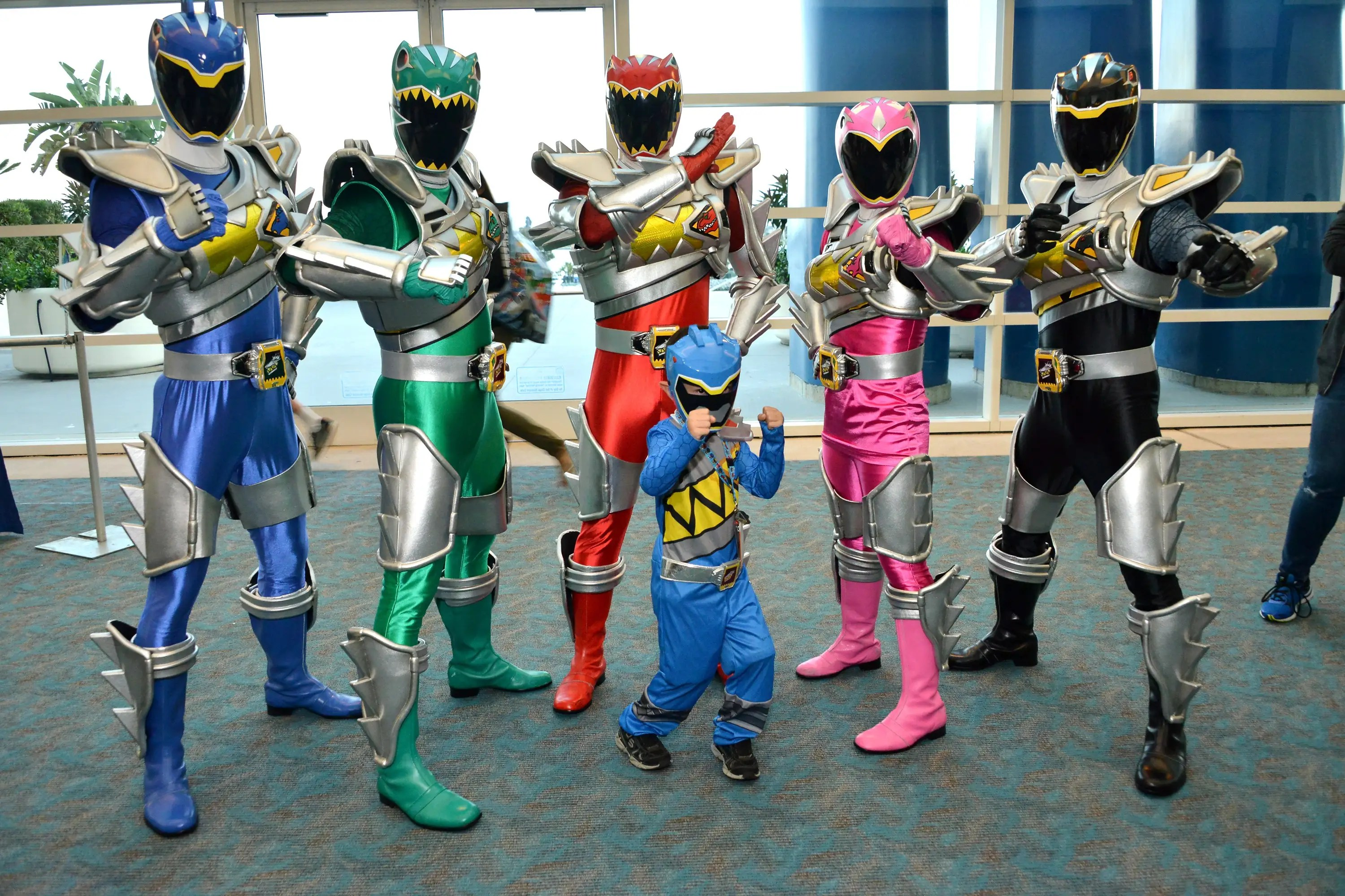 It's Morphin Time! Power Rangers Dino Super Charge characters pose with a mini Ranger.