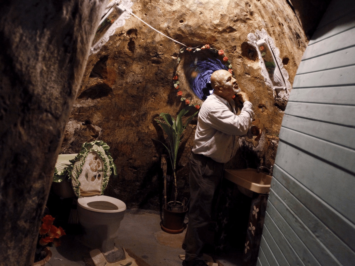 The home contains a bathroom and an underground service, where the family gets water. Here, Barrantes can be seen shaving in the carved restroom.