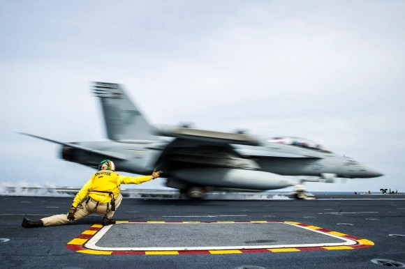 Lt. Chris Denton, a shooter aboard the U.S. Navy's forward-deployed aircraft carrier USS George Washington, gives the signal to launch an E/A-18G Growler from the Shadowhawks of Electronic Attack Squadron 141 during carrier qualifications.