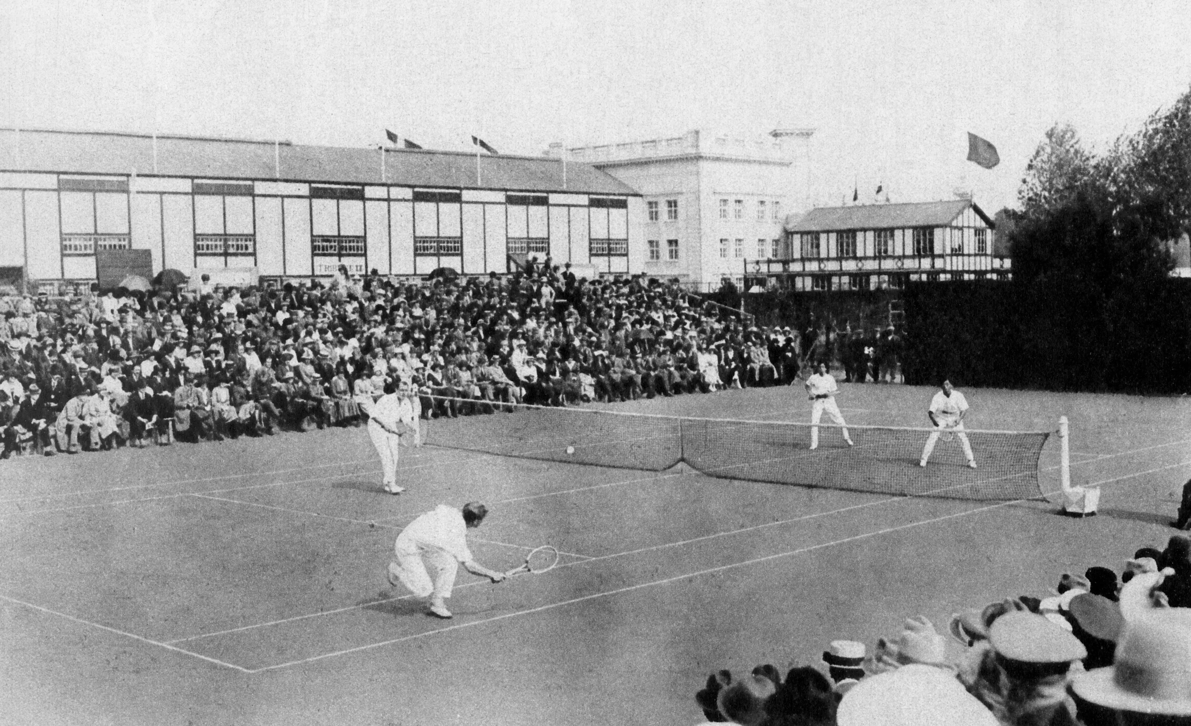 Antwerp, 1920: The Olympics moved to Antwerp in the hope of bringing together a city devastated by World War I. Below, Great Britain's Max Woosnam (top left) and partner Oswald Turnbull play against Ichiya Kumagae and Seiichiro Kashio of Japan. Great Britain won the match to claim the Gold Medal.