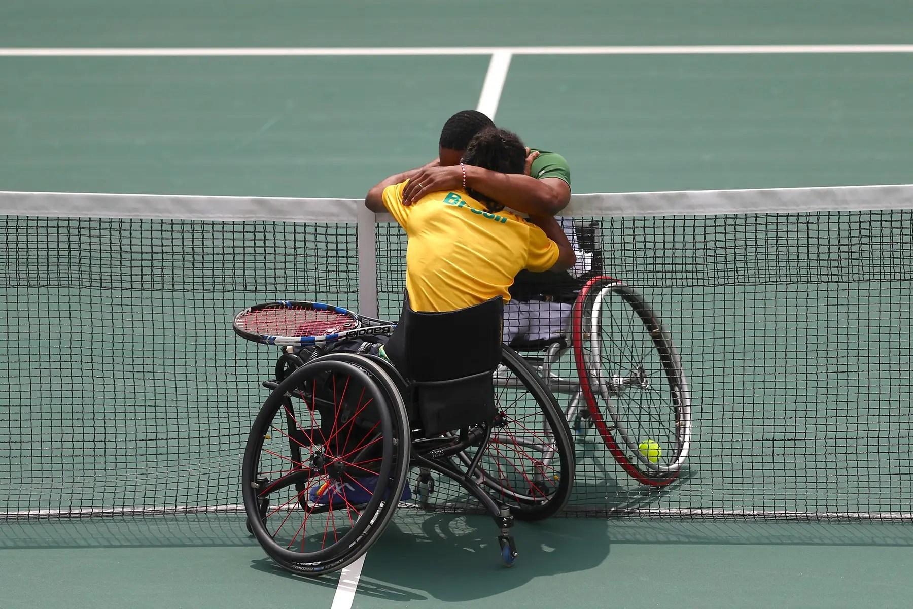 Lucas Sithole de Sudáfrica y Ymanitu Silva de Brasil abrazo después de competir en el tenis en silla de ruedas.