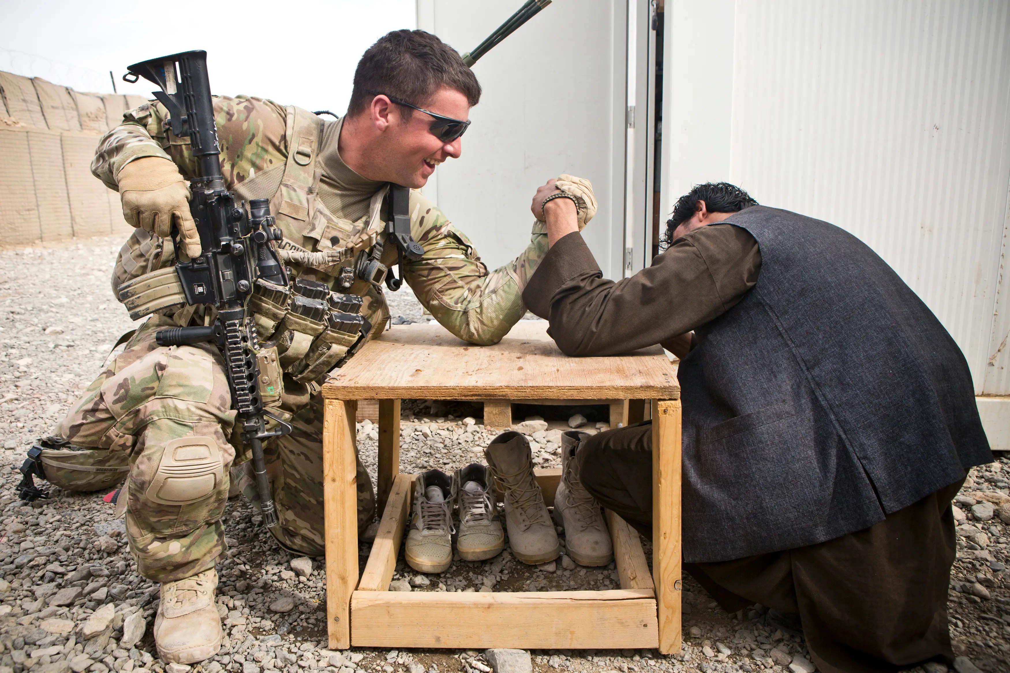 A US Army soldier and a member of the Afghan Uniform Police arm wrestle prior to a joint patrol near Command Outpost AJK (short for Azim-Jan-Kariz, a nearby village) in Maiwand District, Kandahar Province, Afghanistan, January 28, 2013.